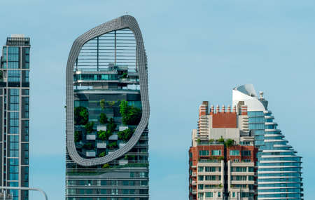 Eco-friendly building in the modern city. Green tree in vertical garden on sustainable glass building for reducing heat and carbon dioxide. Office building with green environment. Go green concept.