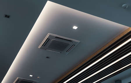 Selective focus on cassette type air conditioner mounted on ceiling wall. Air duct on ceiling in hotel. Air heading unit on gypsum wall. Cool system in the building. Air flow and ventilation system.