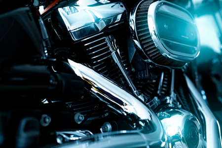 Selective focus on a motorcycle air filter with blur engine and shiny exhaust pipe. Motorcycle dealership business. Shiny chrome motorbike engine and exhaust pipe. Closeup vintage motorbike parts.