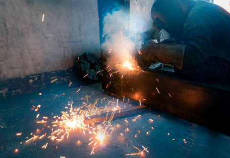Welder welding metal with argon arc welding machine and has welding sparks. Man wears a welding mask and gloves. Safety in industrial workplace. Welder working with safety. Steel industry technology.