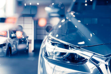 Selective focus grey car parked in luxury showroom. Car dealership office. New car parked in modern showroom. Car for sale and rent business concept. Automobile leasing and insurance background.