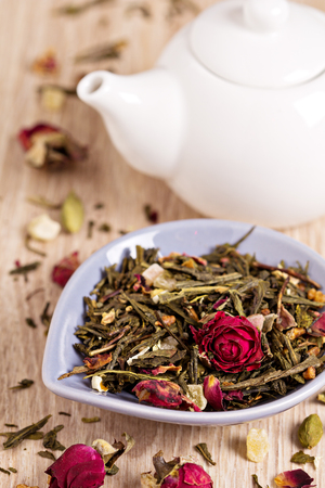 Green tea with fruits, spices, rose petals and bamboo leaves photo
