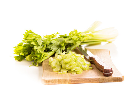 Celery on a cutting board on white background