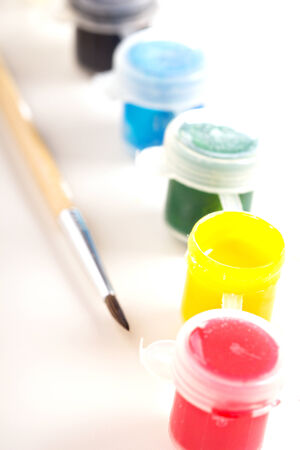 Different paint in small plastic jars with a brush photo