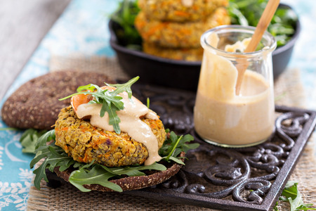Vegan burgers with sweet potato served with arugula and peanut sauce photo