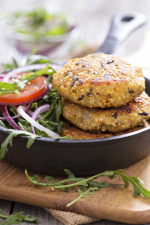 Vegan burgers with quinoa and vegetables served with arugula and salad