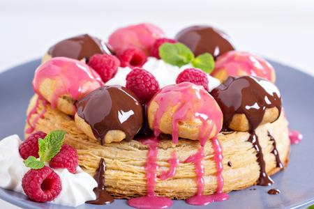 Saint-Honore cake with whipped cream, chocolate and raspberry photo