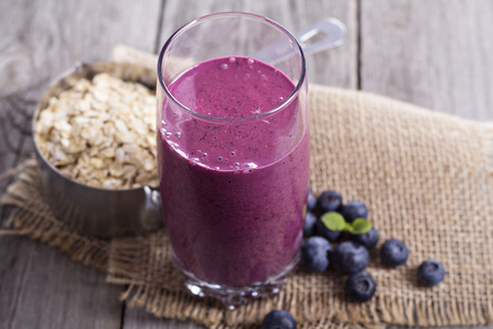 oat: Smoothie with blueberries, banana and oatmeal in a glass Stock Photo