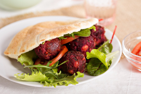 Beetroot falafel served with salad in a pita photo
