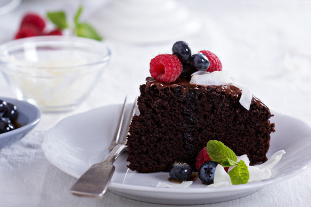 Vegan chocolate cake with berries and coconut on top photo