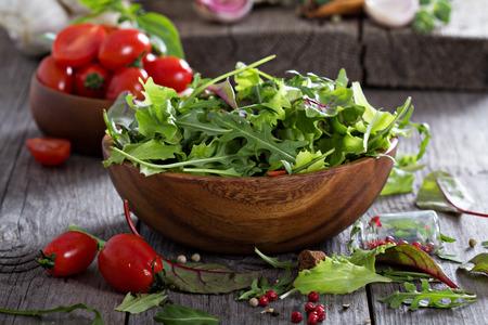 木製のボウルにミックス サラダ緑の葉します。