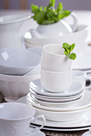 Variety of white dinnerware: plates, cups and bowls