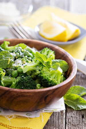 Lemon broccoli with peas and mint in a wooden bowl photo