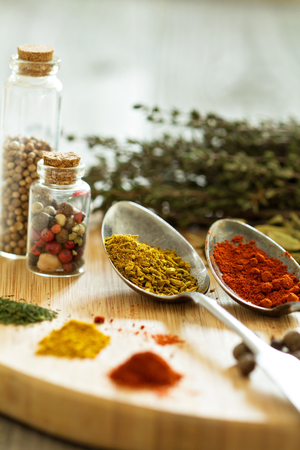 Variety of spices and herb on a wooden board - selective focus photo