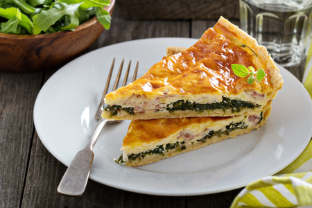 Quiche with cheese, arugula and bacon on a table photo