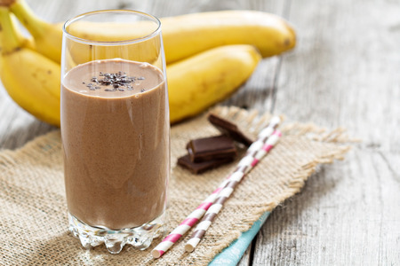 Chocolata banaan smoothie in een glas met rietjes Stockfoto
