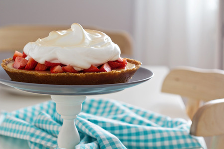 Lemon strawberry meringue pie on a cake stand photo