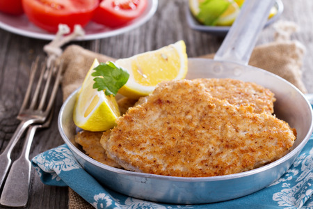 Pork schnitzel with lemon wedges in pan