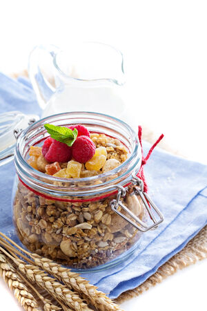 Homemade citrus granola in a glass jar isolated on white photo