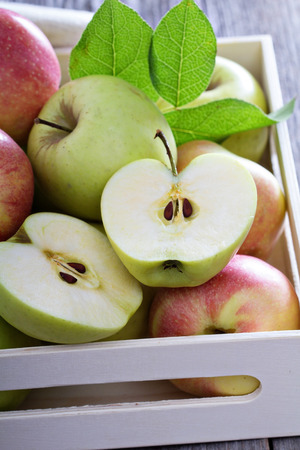 Fresh apples cut and whole in a wooden crate photo