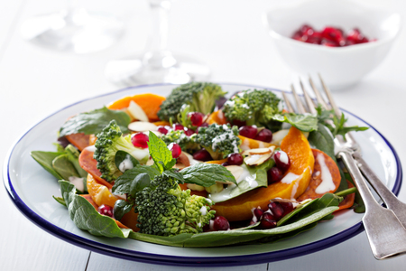 Salad with vegetables, pepperoni and pomergranate photo