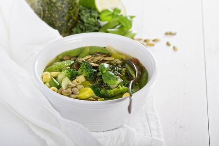 Green minestrone with a lot of vegetables and pasta photo