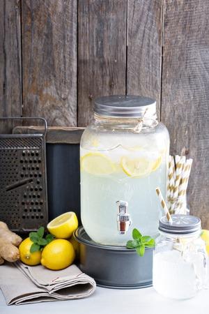 a jar stand: Ginger homemade lemonade in a beverage dispenser Stock Photo