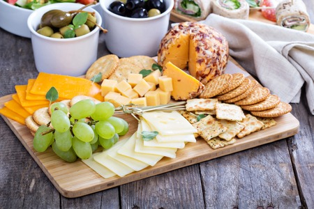 cheese plate: Cheese plate with many foods on a table