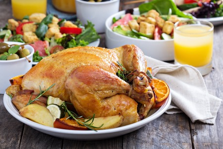 dinner dish: Whole roasted chicken on dinner table Stock Photo