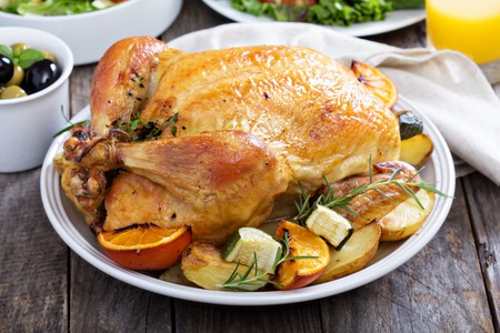 roasted chicken: Whole roasted chicken on dinner table Stock Photo