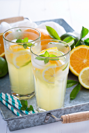 Homemade citrus lemonade in tall glasses with fresh fruits Фото со стока