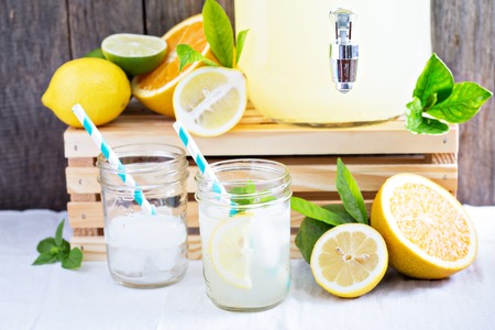 Homemade lemonade in beverage dispencer and mason jars