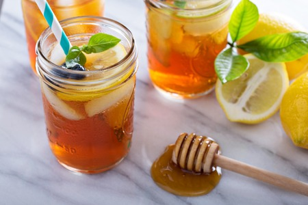 Homemade honey iced tea in mason jars with straws Stock Photo