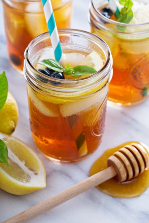 Homemade honey iced tea in mason jars with straws Фото со стока