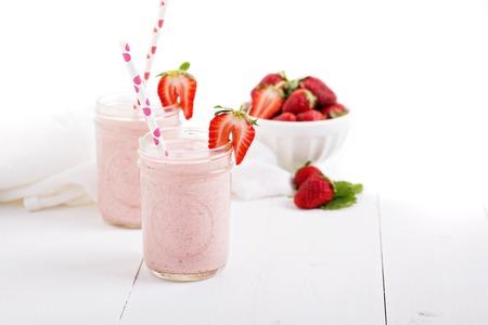 mason: Strawberry milkshake in mason jars on white