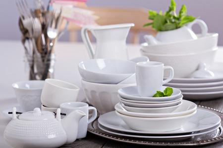 Verscheidenheid van witte servies: borden, kopjes en schalen