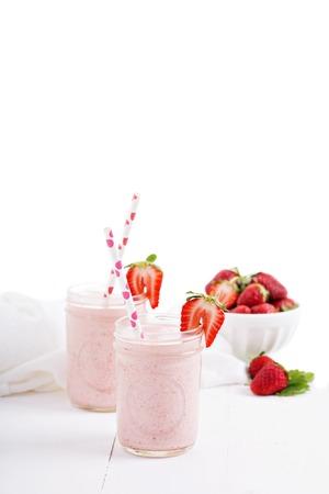 Strawberry milkshake in mason jars on white