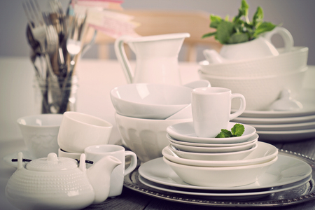 Variety of white dinnerware: plates, cups and bowls toned image