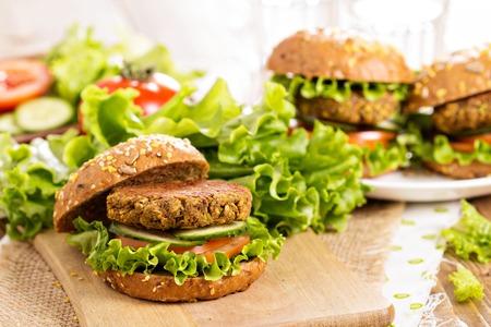 Vegan hamburgers met linzen en pistashios gestapeld op een snijplank