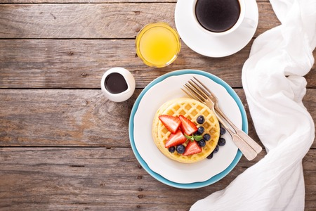 syrup: Breakfast waffles with fresh berries stacked on a plate