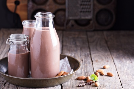 Homemade almond chocolate milk in three bottles