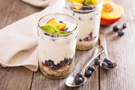 layered: Layered breakfast parfait with granola, peaches and berries