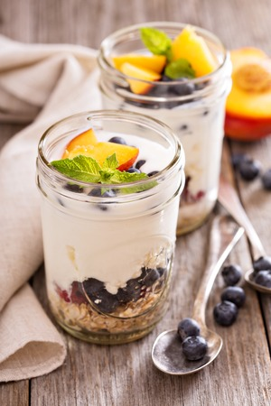parfait: Layered breakfast parfait with granola, peaches and berries