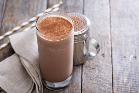 Koude chocolade milkshake in hoog glas met ijs Stockfoto
