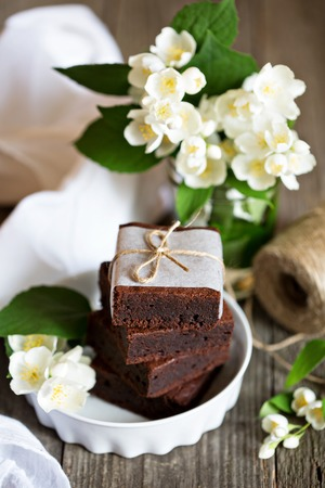 mascarpone: Chocolate mascarpone brownies stacked with flowers on wooden table