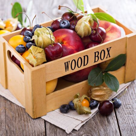 Fresh fruits cherries peaches plums in a wooden crate