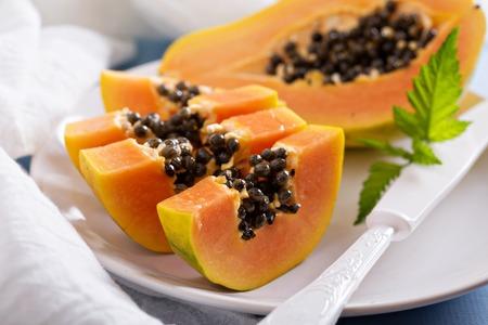 Вырезать папайи экзотические фрукты на синем столе Фото со стока