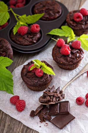 Chocolate raspberry yogurt muffins with pieces of chocolate and muffin tin 스톡 콘텐츠