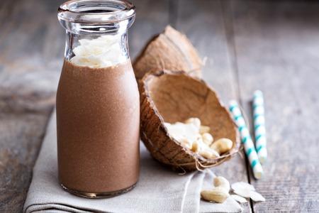 Gezonde veganistische chocolade kokosnoot cashew schudden in een fles Stockfoto