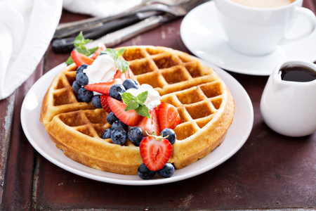 and delicious food: Fresh homemade waffles with ricotta served with whipped cream and berries